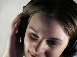 Person som lyssnar på talbok eller ljudbok i ett par hörlurar