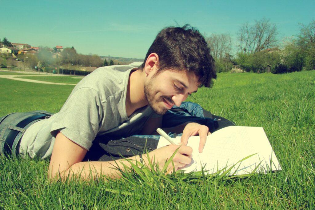 En man som skriver på sitt manus i gröngräset.